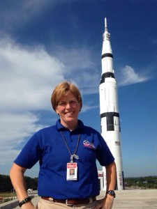 Ruth Marie Oliver (Red Bull) on the Roof of the USSRC with the Saturn V in the Background