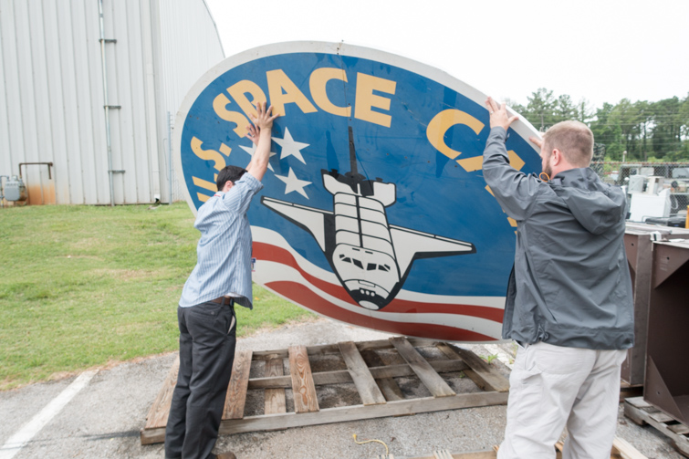 Two people holding the ten foot Space Camp sign